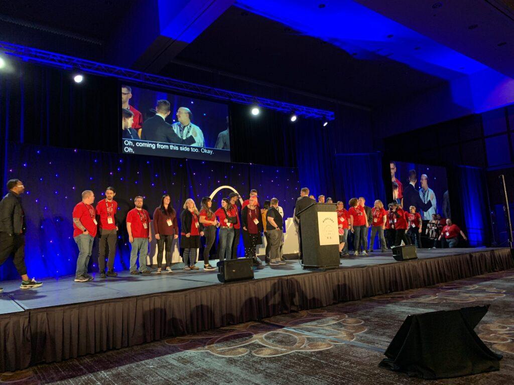 Matt Mullenweg invites WordCamp US volunteers up onto the stage to show thanks.
