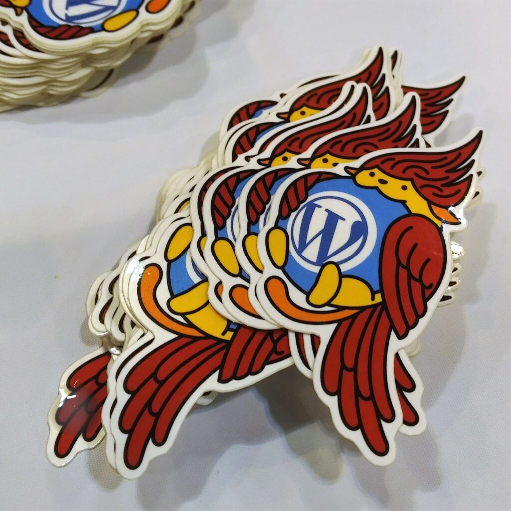 Stickers with Wapuu, the WordPress mascot, dressed as a cardinal, are shown on a table, honoring the host city, St. Louis.